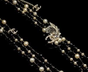 Lunga collana in perle di vetro piccole e grandi di colore bianco e nero modello chanel, con spilla in strass laterale e fermagli Chanel - prezzo